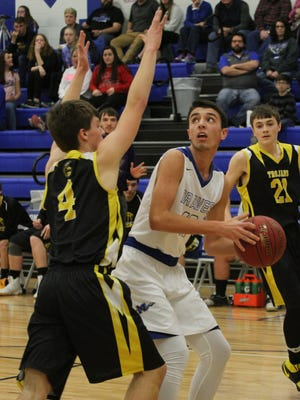 Montezuma's Hunter Ray, 10, looks for the basket as Tri-County's Cameron Krumm, 4, blocks against Montezuma in the opener of the Class 1A-District 11 game on Thursday, Feb. 16. Montezuma won the game 68-43.