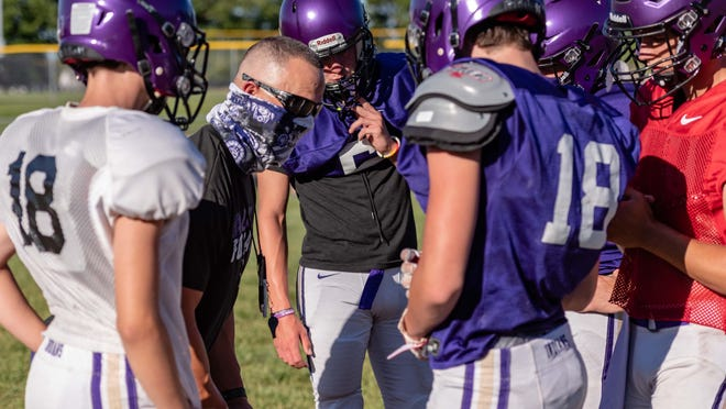 Hallsville head football coach Justin Conyers, second from left, speaks to a huddle of players during preseason practice Wednesday at Hallsville High School.
