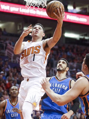 Suns guard Devin Booker (1) goes up for a layup as Oklahoma City forward Doug McDermott (25) defends in the first half at Talking Stick Resort Arena in Phoenix on Friday, April 7, 2017.