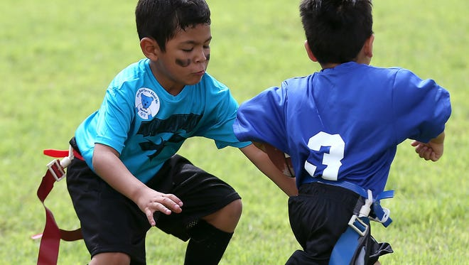 Noah Murillo, 5, pulls another player's flag during a flag football game at River Fest on in 2016.