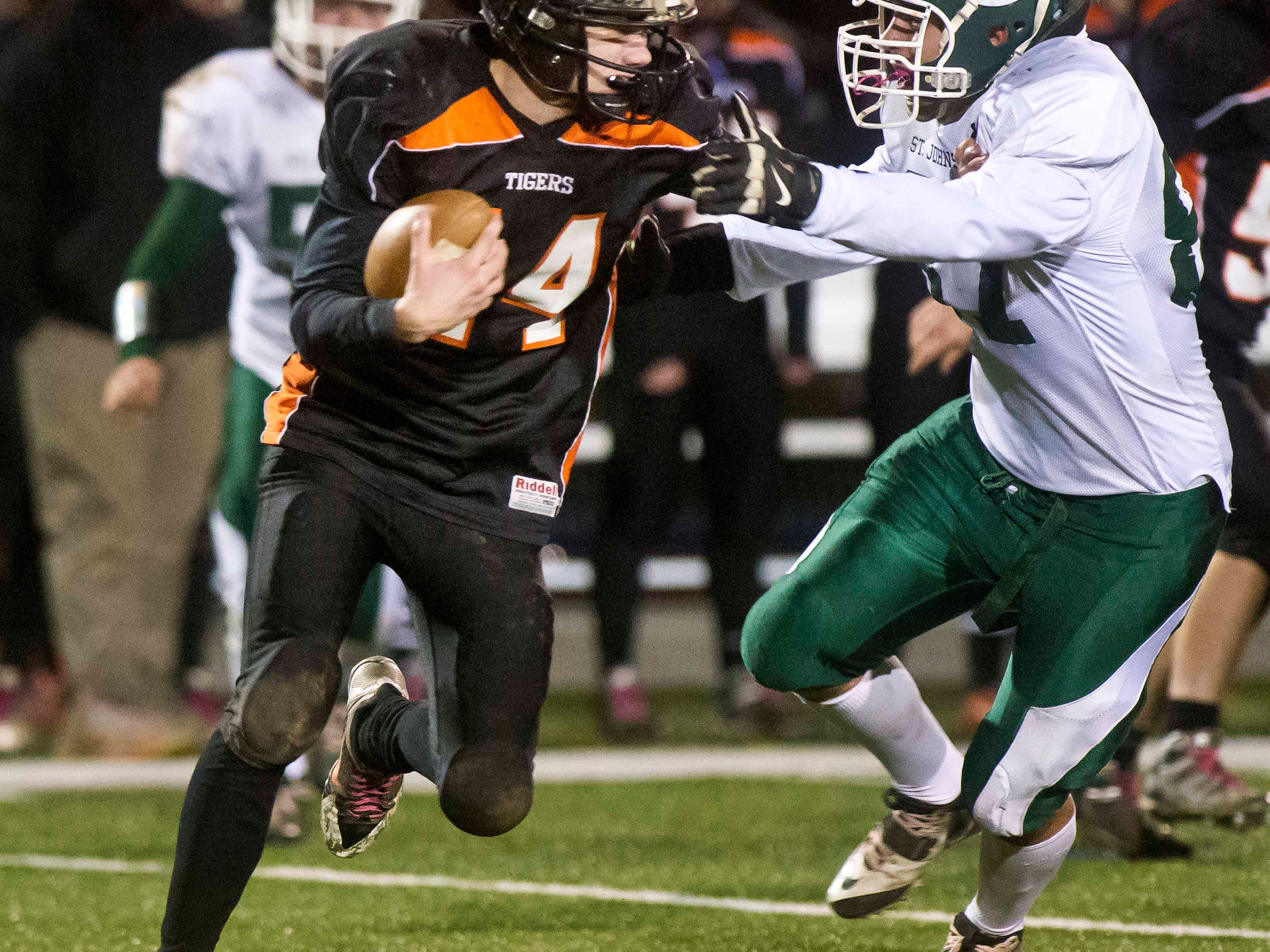 Middlebury's Austin Robinson, left, is pursued by St. Johnsbury's Carlos Carrasco in the Division I football championship game in Rutland on Nov. 8.