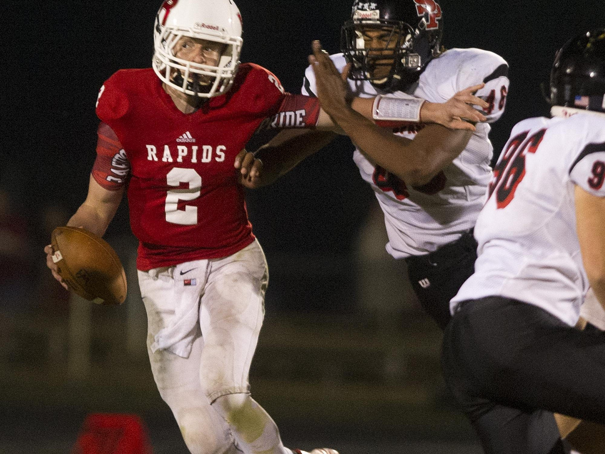 Wisconsin Rapids quarterback Benjamin Olson, left, attempts to fend off SPASH's Patrick Dietzman, right, during the Wisconsin Valley Conference football game against SPASH at South Wood County Recreation Center in Wisconsin Rapids, Friday, Sept. 25, 2015.