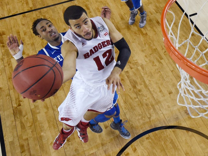 Wisconsin guard Traevon Jackson (12) drives to the basket past Kentucky guard James Young during the second half of an NCAA Final Four tournament college basketball semifinal game Saturday, April 5, 2014, in Arlington, Texas. Kentucky won 74-73. (AP Photo/Chris Steppig, pool)