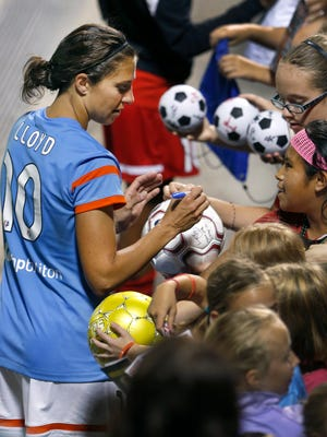 Houston's Carlie Lloyd signs autographs for fans after her 1-0 winning goal in the second half.