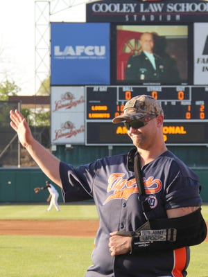 Sgt. Jordan LaRoche, of Lansing, Army National Guard, waves to the crowd at a Lugnuts game last summer during his video-board salute as a LAFCU Community Champion.