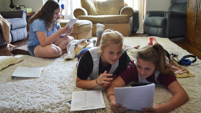 Emma Hirneise, 13, left, and Grace Bradfield, 13, center, practice for an upcoming church play with their friend, Paige Lewis, 12, at Bradfield's home. Emma and Grace will be one of the dozens of homeschoolers participating in classes in the new Homeschoolers of Ottawa County Christian Co-op this fall.