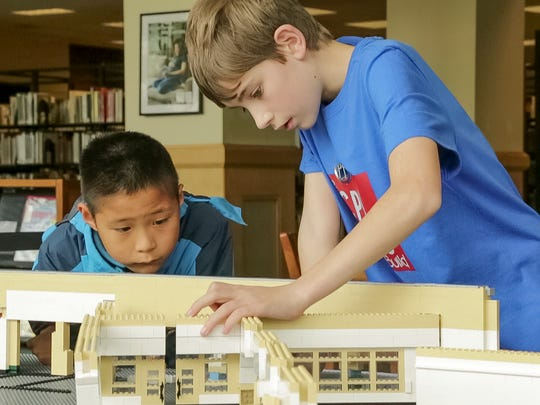 Nine-year-old Terry Wang watches as 12-year-old Andrew McCracken puts a wall into place. The doors in the wall are the entrance to the Ezra Cornell Reading Room at the at the far end of the Avenue of Friends from the entrance.