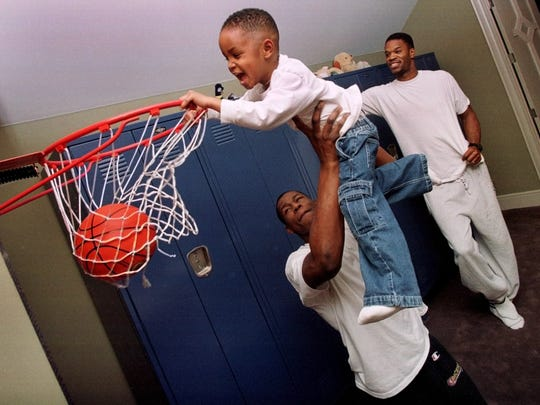 A.J. Davis, 3, hangs on the rim with the help of Pacers rookie Al Harrington (center) and Pacers veteran Antonio Davis (right) look on at Davis' home  Jan. 19 1999. Harrington has been staying with Davis during the lockout and will continue to stay with his family throughout the NBA season.
