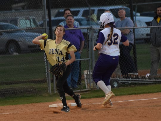 Jena's third baseman Peyton Hebron (14, left) throws to first after tagging third for an out against ASH's Carrie Boswell (32, right) Thursday.