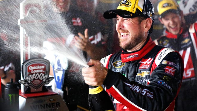 NASCAR Sprint Cup Series driver Kurt Busch celebrates in victory lane after winning the Quicken Loans 400 at Michigan International Speedway on Sunday.