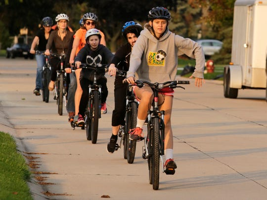 Seniors with cognitive disabilities at the Sterling Heights High School ride bikes in the community close together to learn how to quickly stop and pass directions to each other as they participate in a PEAC program to help them be more confident riding a bicycle and taking public transportation on Tuesday, October 18, 2016.
