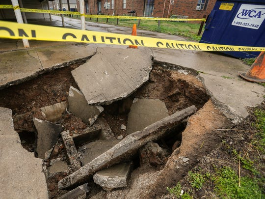 A trash truck fell into a hole after the concrete collapsed underneath him at an apartment complex near E. University Street on Monday, April 2, 2018.