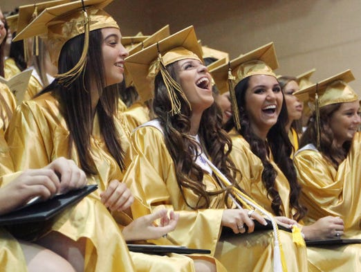 Danielle Bernardo, center, of Bishop Verot, laughs as the commencement address is delivered by Allison Oliva during graduation ceremonies at Bishop Verot High school on Saturday.