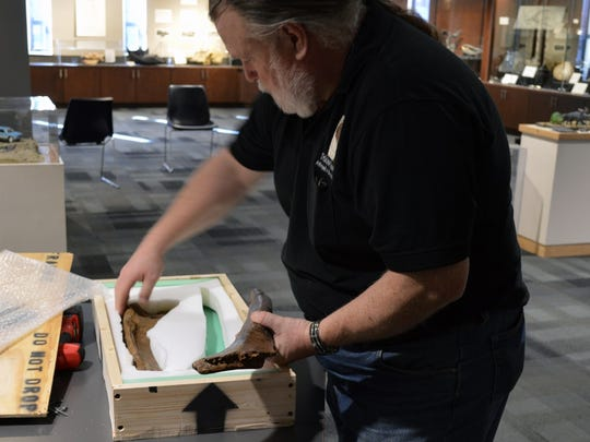 """Paleontologist Joseph """"PaleoJoe"""" Kchodl removes dinosaur fossils from a packing box at the Nasr Natural Science Museum."""