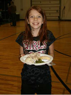 A girl carries a plate of Thanksgiving food at a past Feast, hosted by the Boys & Girls Club of the Wausau Area.