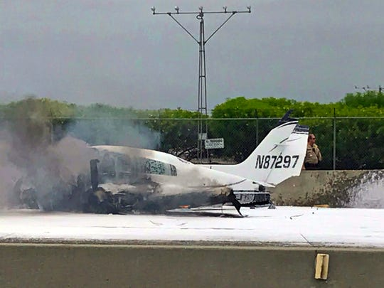 Flame and smoke erupt from a twin-engine prop jet after it crashed on Interstate 405, just short of the runway at John Wayne Orange County Airport, rear, in Costa Mesa, Calif., Friday, June 30, 2017. Officials said two people were injured and were taken by helicopter to a hospital. The freeway was shut down in both directions.