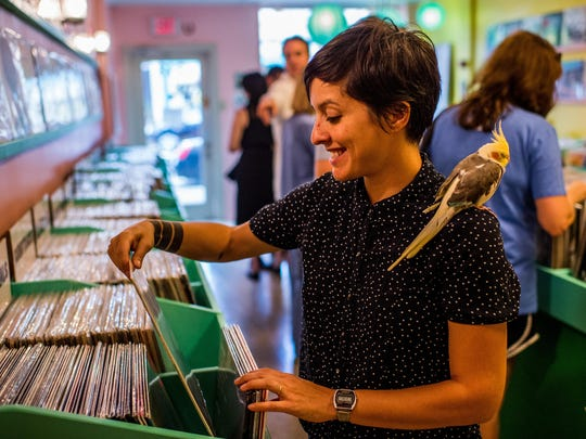 Store co-owner Tess Brunet, joined by her pet cockatiel Agnes, sorts albums at Lagniappe Records on Friday. Brunet and co-owner Patrick Hodgkins moved the business from Baton Rouge.