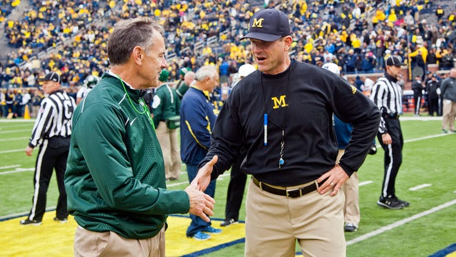 Michigan State football coach Mark Dantonio, left, shakes hands with Michigan coach Jim Harbaugh before a game in Ann Arbor on Oct. 17, 2015.