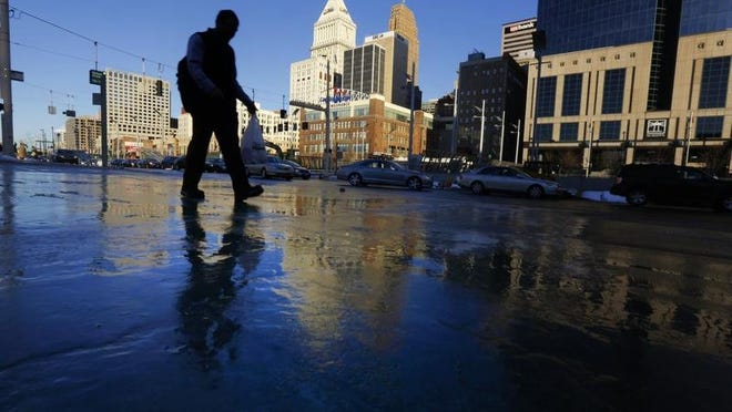 Chris Schmoyer of Linwood navigates icy sidewalks as he walks to work along Third Street Downtown.