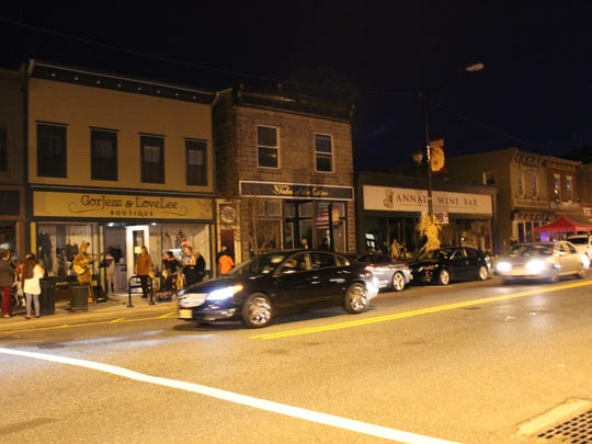 Cars pass a darkened Bellevue Avenue during the power outage during Third Thursday.