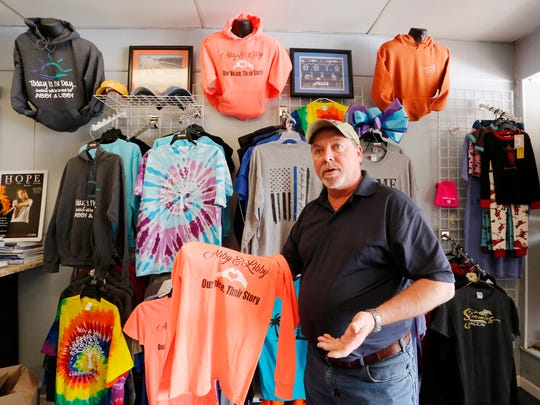 Mark Mendel shows shirt designs in honor of Liberty German and Abigail Williams Tuesday, February 6, 2018, at Hometown Shirts & Graphix in Delphi. German and Williams were murdered February 13, 2017, while hiking the Monon High Bridge Trail just east of Delphi. Proceeds from the sale of the shirts go to the Libby & Abby Softball Park.