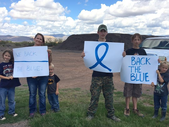 Alamogordo Police Department Capt. Mike Lawrence's family shows their support for law enforcement as the escort guarding fallen officer Clint Corvinus leaves Alamogordo on their way to Albuquerque.