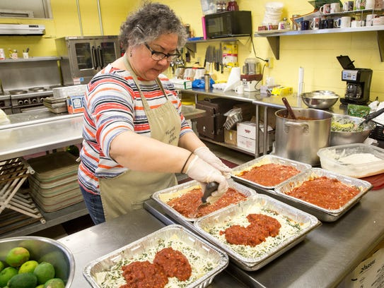 Gerri Airriess works on preparing 40 trays of lasagna