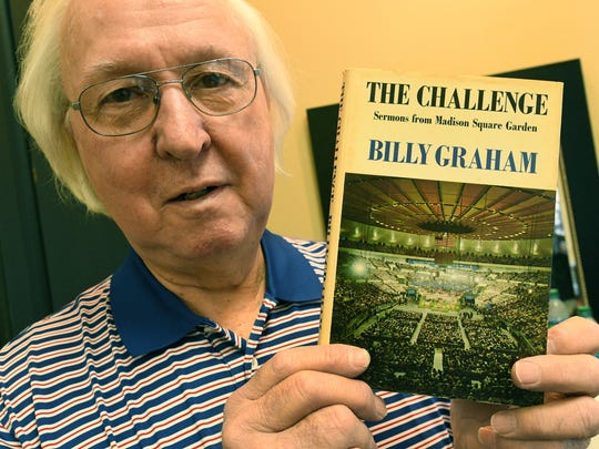 Barber Cecil Groce holds a book signed by Billy Graham