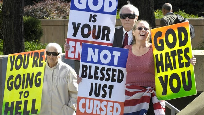 Margie Phelps, left, stands with her husband, Pastor Fred Phelps, and her daughter Margie J. Phelps during a demonstration outside the federal courthouse in Baltimore on Oct. 31, 2007.