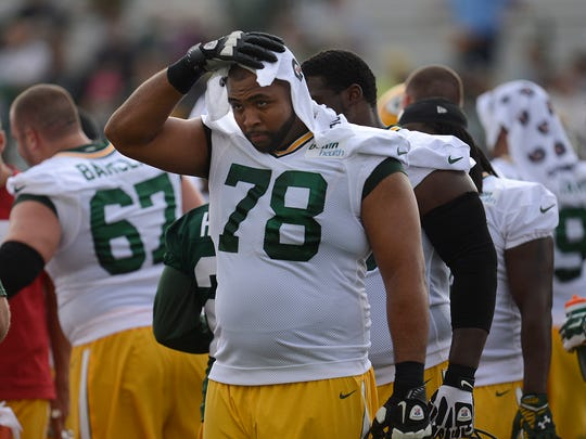 Green Bay Packers tackle Derek Sherrod (78) cools off with a towel during training camp practice at Ray Nitschke Field on Saturday, July 26, 2014.