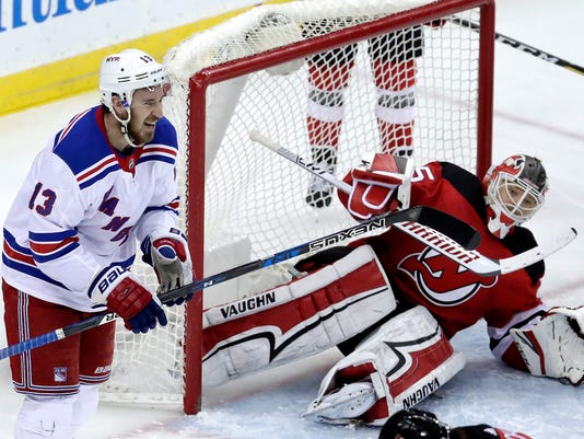 New York Rangers center Kevin Hayes (13) reacts after scoring a goal on New Jersey Devils goalie Cory Schneider, right, during the third period of an NHL hockey game Thursday, Dec. 21, 2017, in Newark, N.J. The Devils won 4-3 in a shootout. (AP Photo/Julio Cortez)