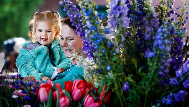 Maria Parham (right) picks flowers with her granddaughter Kenzie Bourquin, 2, (left) during the first day of the Downtown Farmers Market, located in Historic South Main District.