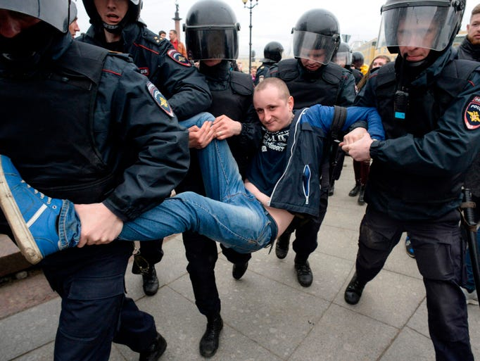 Russian police officers detain a protester during an