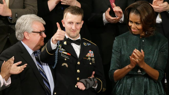 Army Ranger Sgt. 1st Class Cory Remsburg acknowledges applause from first lady Michelle Obama and others during President Obama's State of the Union address on Capitol Hill in Washington on Jan. 28, 2014.