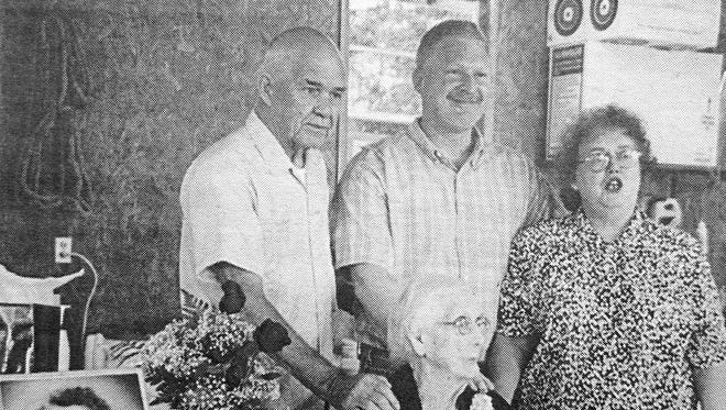 Eula Holden at her 100th birthday party. From left, Lester Holden, Les Holden and Margie Griffith stand at Eula's side. On the table is a portrait of Eula taken in 1953.