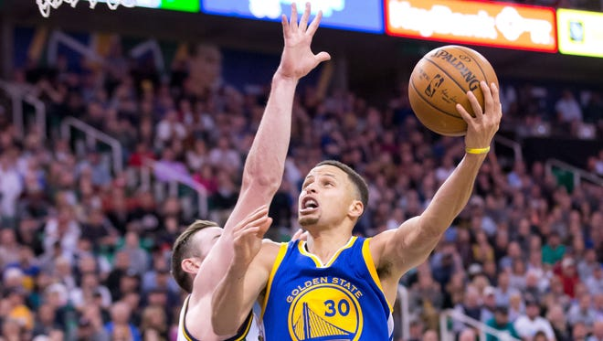 Golden State Warriors guard Stephen Curry goes up for a shot against Utah Jazz forward Gordon Hayward (20) during overtime at Vivint Smart Home Arena. Golden State won 103-96.