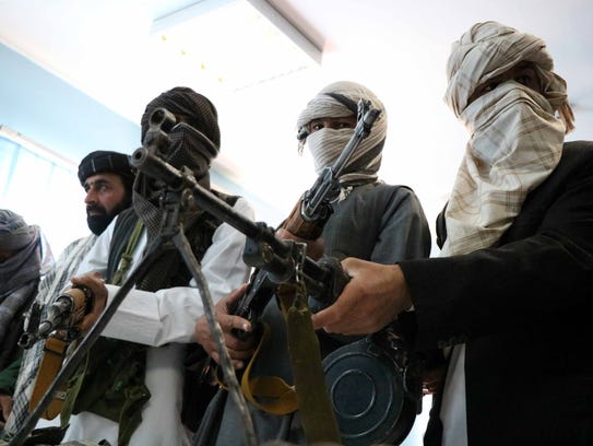 Former Taliban members surrender their weapons during