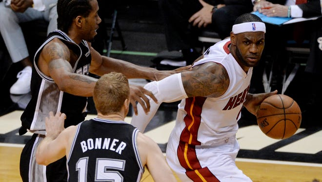 Heat forward LeBron James (right) tries to escape the defense of Spurs forward Kawhi Leonard (left) and forward Matt Bonner during Game 4 of the NBA Finals on Thursday.