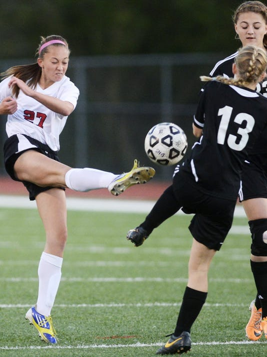 Dover's Paige Hartman kicks the ball through Northeastern's Rachel Nagel (13) and Coryn Moyer during a Sept. 17 girls' soccer match in Dover. (DAILY RECORD/SUNDAY NEWS -- KATE PENN)