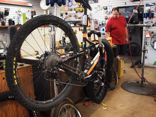 A bike sits on a repair stand while store manager Justin