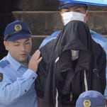 Police officers escort Kenneth Shinzato, an American working on a U.S. military base in Okinawa, to turn him over to the prosecutor's office on suspicion of abandoning a woman's body.