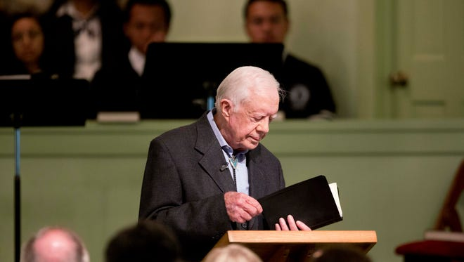 Former President Jimmy Carter opens up a Bible while teaching Sunday School class at Maranatha Baptist Church in his hometown Sunday, Aug. 23, 2015, in Plains, Ga. The 90-year-old Carter gave one lesson to about 300 people filling the small Baptist church that he and his wife, Rosalynn, attend. It was Carter's first lesson since detailing the intravenous drug doses and radiation treatment planned to treat melanoma found in his brain after surgery to remove a tumor from his liver. (AP Photo/David Goldman)