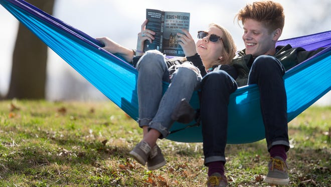 Shaina Rovenstine (left), and Eric Dyer share a book at Garfield Park in Indianapolis while on a break from college.