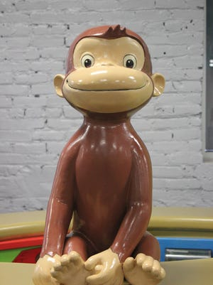 """Curious George comes to life in downtown Lansing, in the interactive exhibit """"Curious George: Let's Get Curious!"""" at Impression 5 Science Center."""