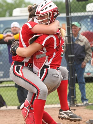 Ashley Riley jumps into the arms of catcher Maddy Rathbun to celebrate the Rockets 4-0 victory Saturday over Maumee in the district final at Genoa.