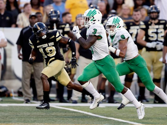North Texas running back Jeffery Wilson (3) runs past Southern Miss' Curtis Mikell during last week's contest at M.M. Roberts Stadium.