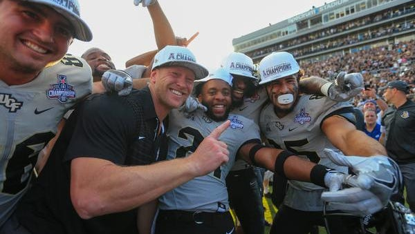 UCF Knights head coach Scott Frost celebrates with players after defeating the Memphis Tigers in double overtime at Spectrum Stadium.