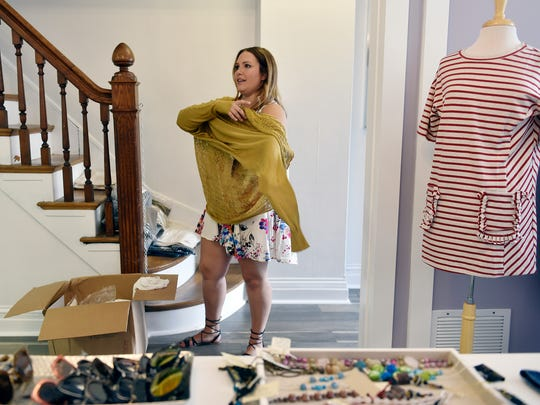 Rebecca Wattenschaidt, owner of Elizabeth & West Fashion House, shows a new fall sweater she'll have for sale soon. Local shops will show off their new fall items during the fifth annual Boutique Week, Aug. 30 to Sept. 3.