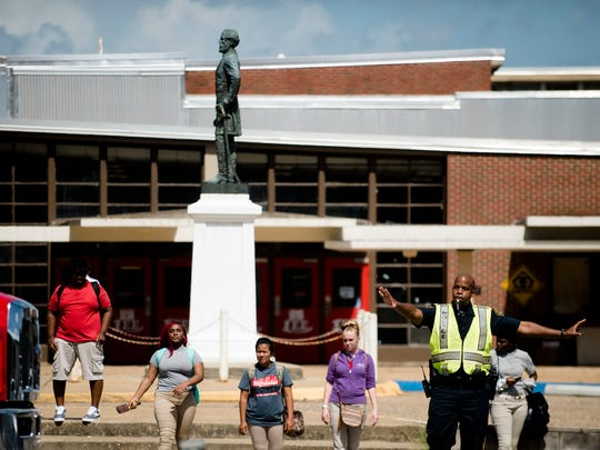 Lee High School students walk past the statue of General Robert E. Lee, who the school is named after, on Thursday, Aug. 17, 2017, in Montgomery, Ala.