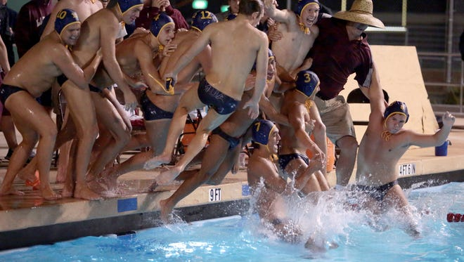 The La Quinta water polo team take their coach for a celebratory plunge after beating Palm Desert 12-8 in the DVL finals on Wednesday at Palm Desert High School.